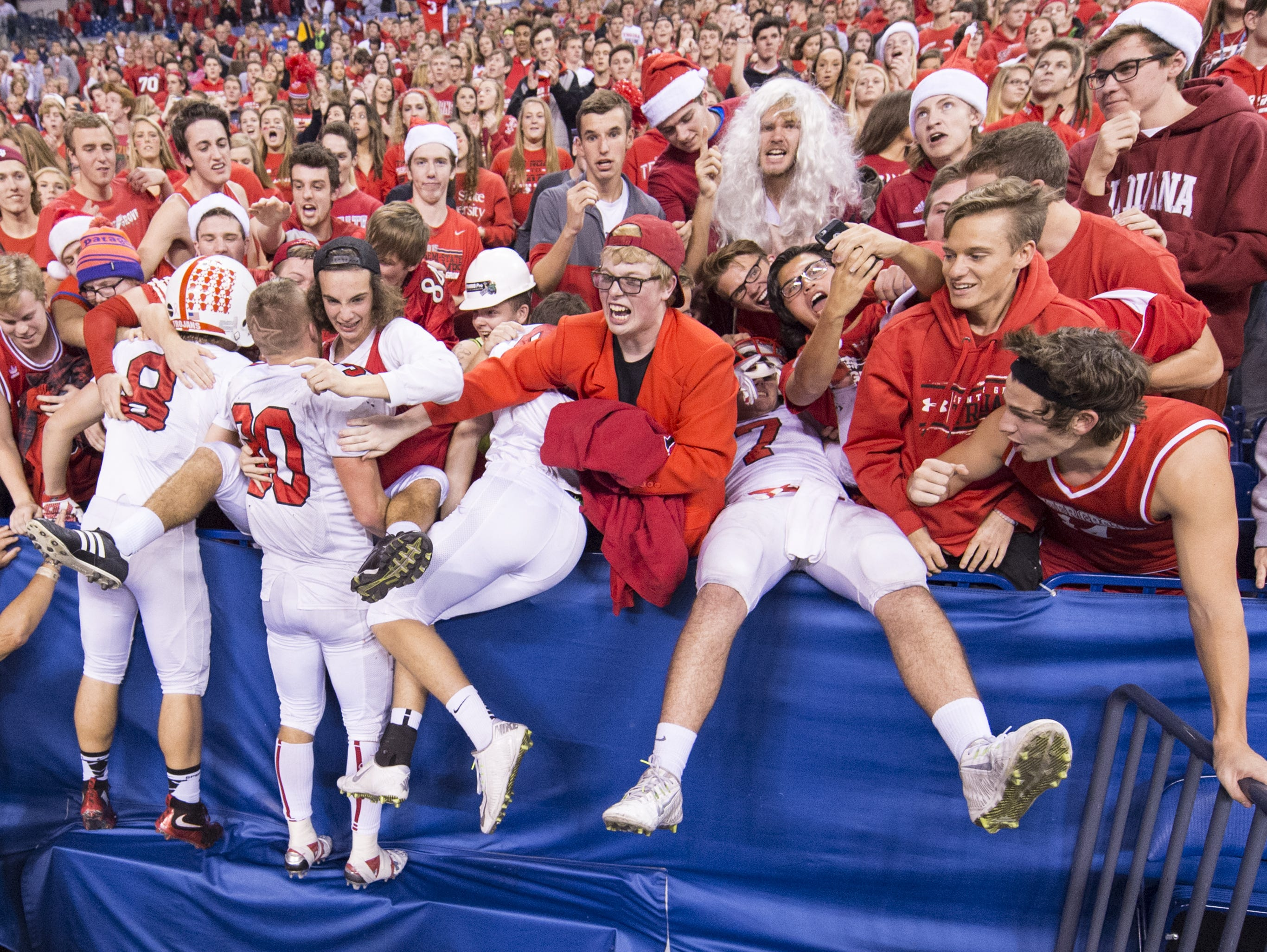 Center Grove players fly into the stands to celebrate winning the IHSAA Class 6A State Championship game with their fans, Saturday, Nov. 28, 2015, at Lucas Oil Stadium in Indianapolis. Center Grove won 28-16, to complete an undefeated season.