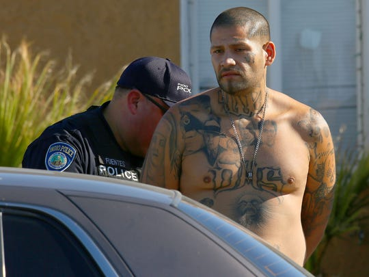 A man is taken into custody by police at a home on