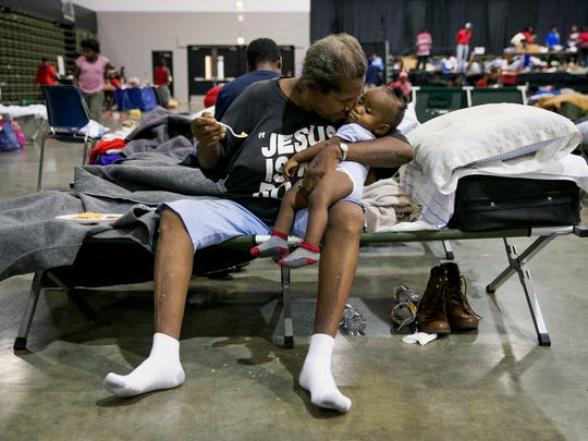 Barbara Coleman feeds 10-month-old Landon Davis, a family friend who shares her home, at an emergency shelter at the Beaumont Civic Center in Beaumont, Texas, after Tropical Storm Harvey on Wednesday, Aug. 30, 2017. Their home in Port Arthur was flooded Wednesday morning.