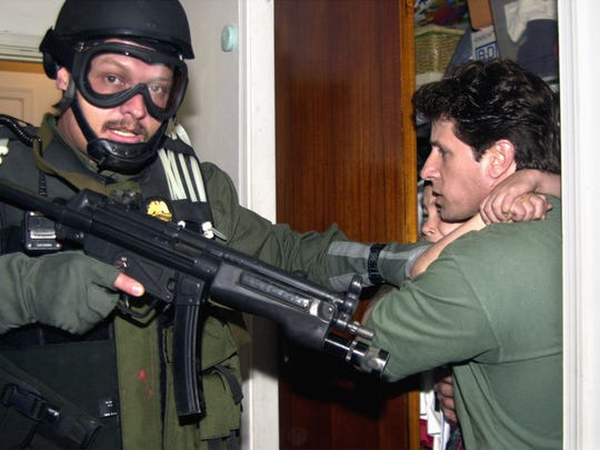 Donato Dalrymple carries 6-year-old Elian Gonzalez from a bedroom closet Saturday, April 22, 2000, past a U.S. Border Patrol agent after federal agents stormed the Miami residence during the early morning hours and seized the boy for a reunion with his father.