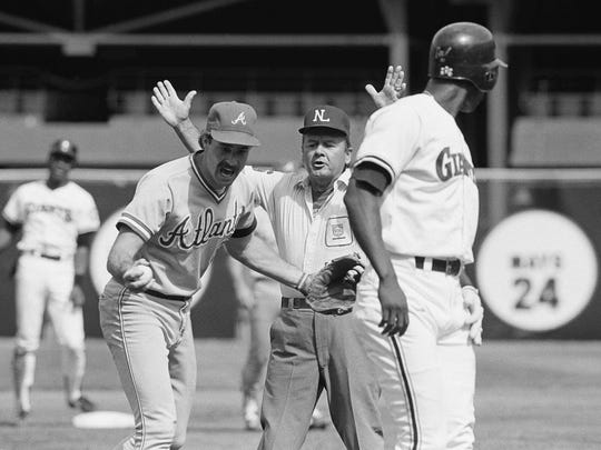 Atlanta Braves' Randy Johnson, left, argues the call of safe at third base with second base umpire Dutch Rennert, center, as San Francisco Giants' Chili Davis looks back during a Sept. 10, 1984, game in San Francisco.