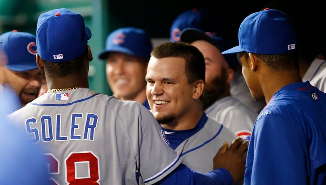 Chicago Cubs catcher Kyle Schwarber (12) is surrounded by teammates after hitting the eventual game-winning home run off Cincinnati Reds relief pitcher Nate Adcock (58) during the thirteenth inning, July 21, 2015, in Cincinnati.
