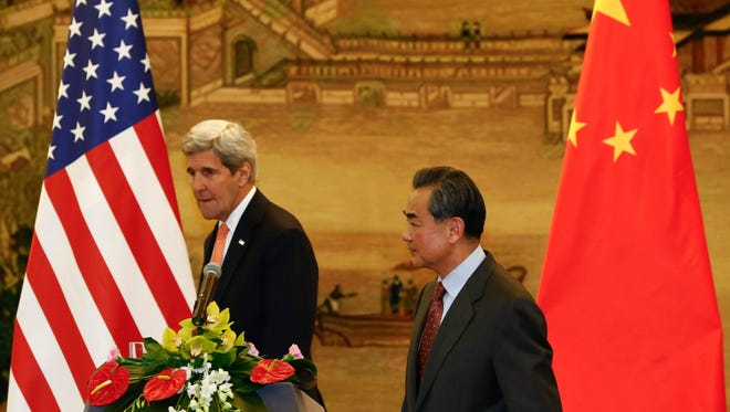 Secretary of State John Kerry and Chinese Foreign Minister Wang Yi make their exit after a joint press conference at the Chinese foreign ministry in Beijing, China, 27 Jan. 2016.