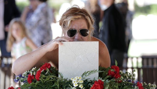 """Angie Sutton kisses her grandfather Maynard L. """"Beamy"""" Beamesderfer's urn during his graveside service Friday at the Fort Bliss National Cemetery. Beamesderfer was a member of the 101st Airborne and one of the Pathfinders who were the first to jump into Normandy on D-Day."""