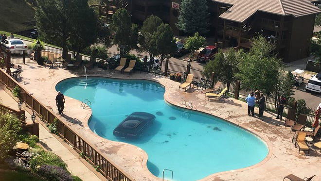 In this photo provided by KKTV 11 a car sits in a pool after a woman escaped injury when she hit the gas pedal instead of the brakes and ended up in the pool at the Cheyenne Mountain Resort, in Colorado Springs, Colo., on Monday morning, July 3, 2017. (Kyla Galer/KKTV 11 via AP)