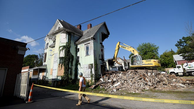 Demolition started Thursday on a Park Avenue West eyesore by the Richland County Land Bank. The structure, 330-334 Park Avenue West, included a large, mint-green, Victorian-style house, a brick structure attached to the front of it and a two-story white house with red doors on the back of the property.