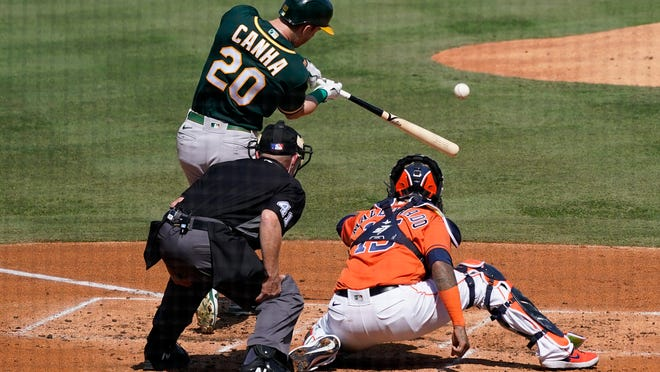 The Athletics' Mark Canha hits a solo home run off in front of Astros catcher Martin Maldonado and umpire Jerry Meals during the second inning of Game 3 of an American League Division Series in Los Angeles.