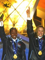 SAT LAKE CITY, UNITED STATES:  Vonetta Flowers (L) and Jill Bakken (R) of the USA celebrate their gold medals in the Women's Bobsleigh competition during ceremonies at the XIX Winter Olympics 20 February 2002 in Salt Lake City, Utah.