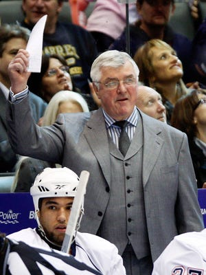 Coach Pat Quinn waves from behind the Edmonton Oilers bench during a 2010 game.