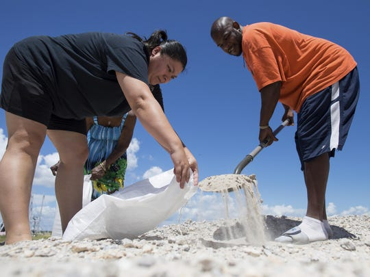 Anthony Rayford and Alma Longbotham fill a sandbag behind the Seaman's Memorial Tower in Aransas Pass, Texas, ahead of a tropical storm on Aug. 23, 2017.
