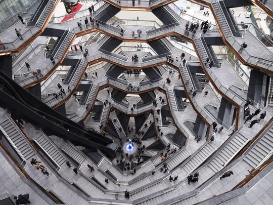"""Visitors to """"Vessel"""" climb its staircases on its opening day at Hudson Yards, Friday, March 15, 2019, in New York. Hudson Yards, a $25 billion urban complex on Manhattan's west side, is the city's most ambitious development since the rebuilding of the World Trade Center."""
