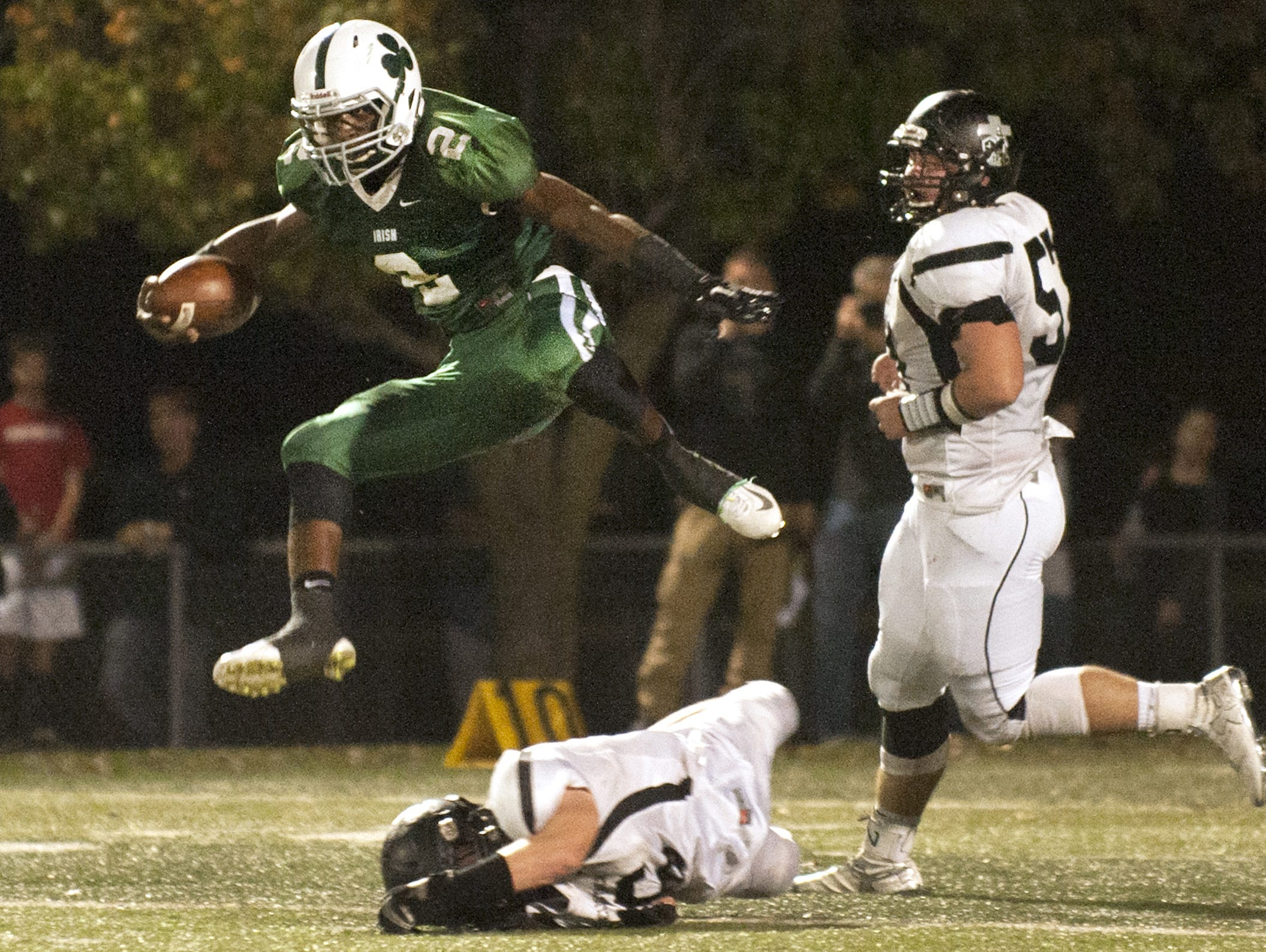 Camden Catholic's Tyree Rodgers leaps over Bishop Eustace's Jack Smith as Rodgers runs the ball during the 2nd quarter of Friday's game.