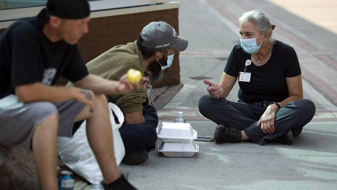 """Lisa Wahoff, a nurse practitioner with the Mount Carmel Health System's street medicine team, talks with a 36-year-old man who preferred to go by the name """"Shaggy""""; beside him is Jesse Erwin, 36. Wahoff was delivering meals to the men outside a convenience store near Ohio State University earlier this month."""