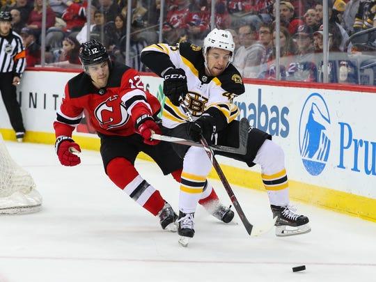 Boston Bruins defenseman Matt Grzelcyk (48) and New Jersey Devils defenseman Ben Lovejoy (12) battle for the puck during the first period at Prudential Center.