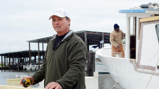 Bert Ducote measures a piece of lumber for his boat, which is being rebuilt at the Lake Catherine Marina in New Orleans, Friday, March 7, 2014. Ducote has had dozens of boils pop up on his skin since performing cleanup work during the Deepwater Horizon oil spill. (AP Photo/Andrea Mabry)