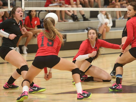Indians players lunge for the ball as Palm Springs defeats Xavier Prep in straight sets on Tuesday at Xavier.