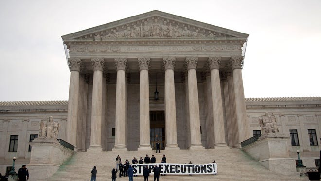 Demonstrators hold a banner on the steps of the Supreme Court during a 2012 protest against the death penalty.