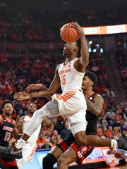 Clemson's John Newman lll (15) drives to the basket while defended by Louisville's Malik Williams during the first half of an NCAA college basketball game Saturday, Feb. 15, 2020, in Clemson, S.C. (AP Photo/Richard Shiro)