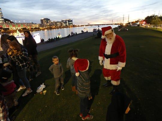 Santa greets children on the shore prior to the Fantasy