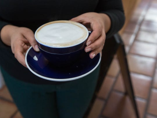 Valerie Mirelez, a barista at Becks Coffee shop takes a cappuccino out to a customer. Wednesday January 10, 2018.