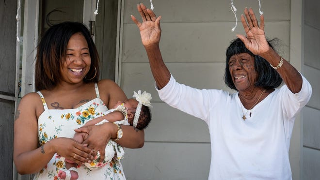 Cora Tyson stands with her great-granddaughter, Chantel Johnson-Graham, who is holding her daughter and Tyson's great-great-granddaughter Micha Johnson-Graham as she waves to well-wishers from the porch of her Lincolnville home on Monday. Tyson was surprised by a birthday parade in honor of her 97th birthday.