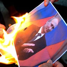 Protesters burn a photo of Russia's President Vladimir Putin during a rally in support of Ukraine and against the Russian President in Tbilisi on August 29, 2014.