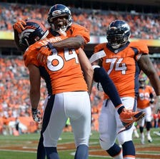 Denver Broncos wide receiver Emmanuel Sanders (10) and tight end Jacob Tamme (84) celebrate a touchdown in the second quarter against the Kansas City Chiefs at Sports Authority Field at Mile High.