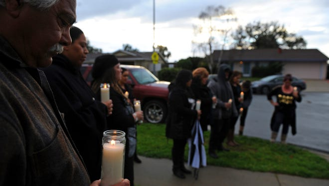 """Family members and friends at Sunday's """"100 Mothers"""" vigil in north Salinas for victims of Monterey County violence."""