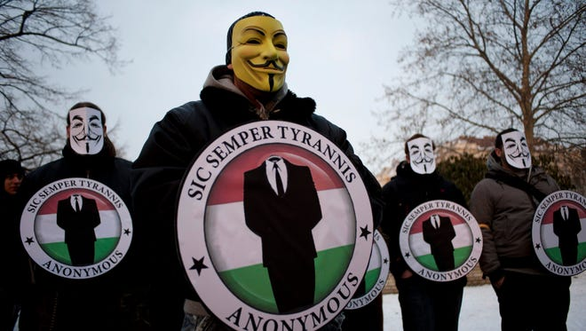 In this Feb. 11, 2012, file photo, protestors wearing Guy Fawkes masks hold the logos of the international hacker group Anonymous during a demonstration against Anti-Counterfeiting Trade Agreement in Budapest, Hungary.  Citing his co-operation with the U.S. government in helping to prevent at least 300 computer hacks against targets in the United States, as well has his help in dismantling computer hacking crew Anonymous, federal prosecutors will ask for leniency when former hacker Hector Xavier Monsegur is sentenced in New York on Tuesday, May 27, 2014.