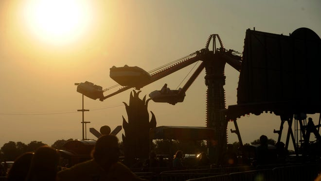 A carnival ride at the Millersport Sweet Corn Festival is silhouetted against the setting sun in this Aug. 31, 2011, photograph. The Millersport Festival has lasted more than 70 years, while other area festivals struggle to survive from year-to-year.