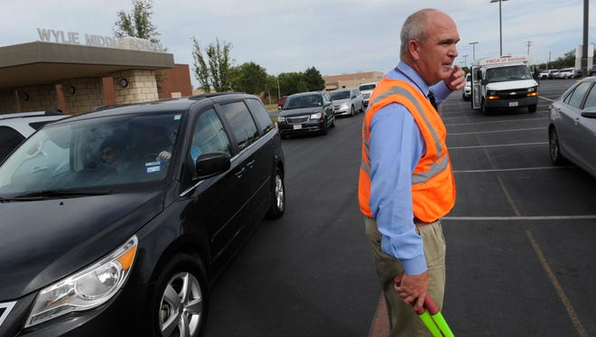 Phil Boone, principal of Wylie Middle School, waves cars through as parents arrive to pick up their children after school. A bond fefore the Wylie Independent School District residents would fund the construction of new facilities and potentially ease congestion around existing schools.