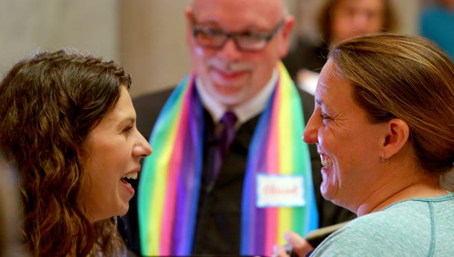 Andria Stock, left, and Chantel Jandak of Jacksonport, Ark., laugh together as they are married May 12, 2014, by Joey Cole, center,  in the rotunda of the Pulaski County Courthouse in Little Rock, Ark.