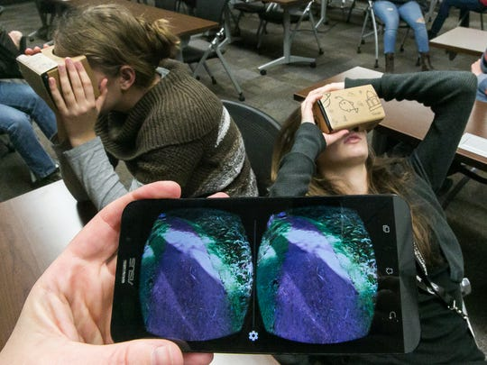 Josephine Sheehan, left, and Hannah Starlet, both 15 years old, use Google Cardboard virtual reality headsets to view a rain forest scene in class on Tuesday.
