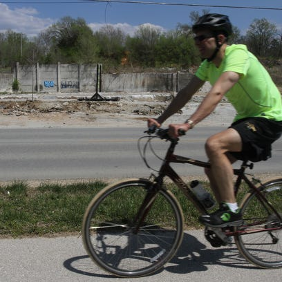 A biker rides on the Galloway Creek Greenway on Friday, April 18, 2014. City Council is considering a proposal that would incentivize development to the north and south of Sequiota Park.