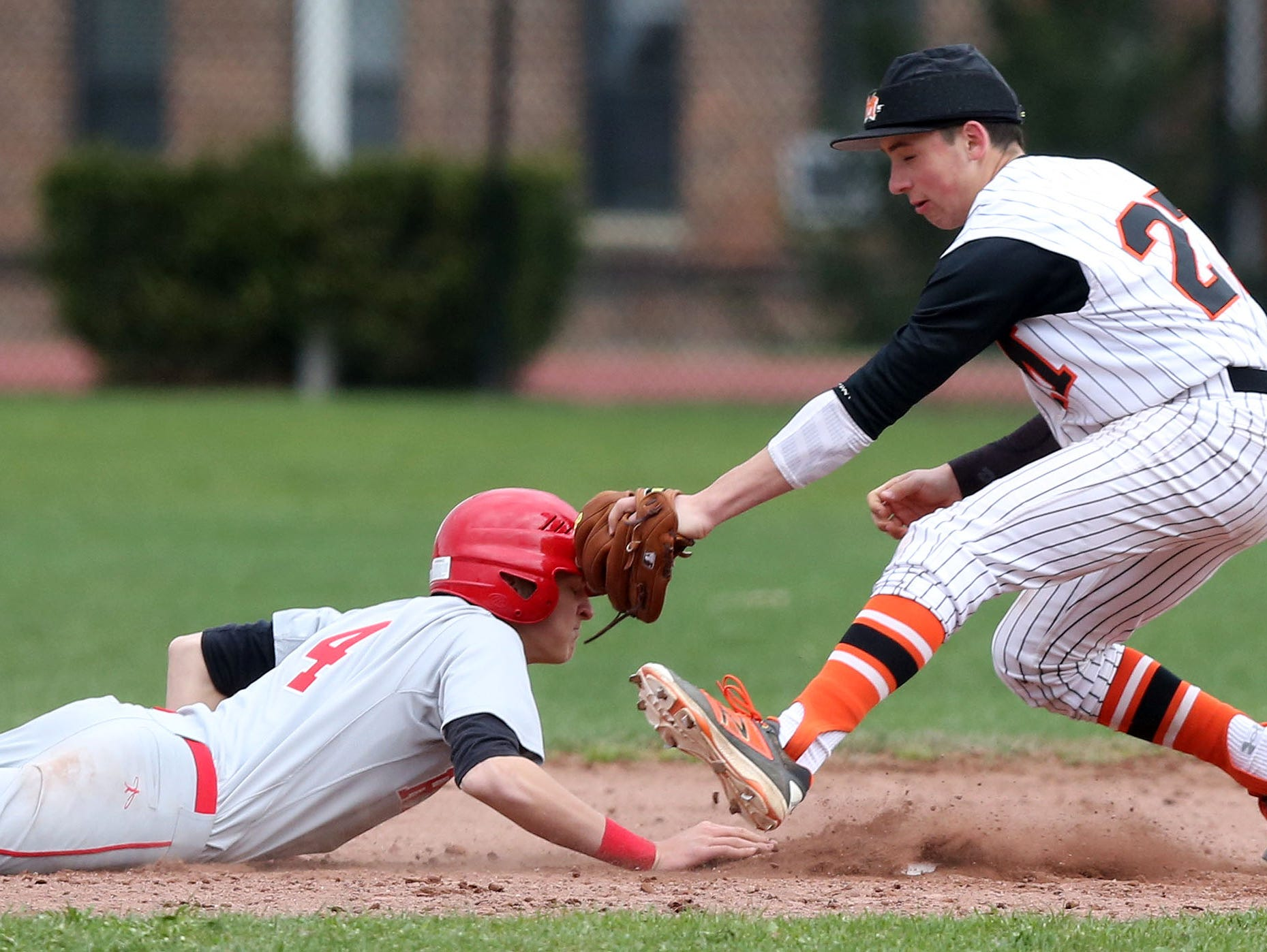 North Rockland's Ken Hoppe (4) dives back to second base on a second inning pick off attempt as Mamaroneck's Mark Adamo takes the late throw during a baseball game at Mamaroneck High School April 6, 2016. North Rockland won the game 4-1.