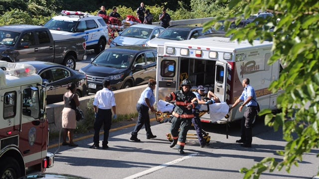 Responders tend to a person injured in a crash on the Bronx River Parkway south of Yonkers Avenue in Yonkers, Aug. 30, 2016.