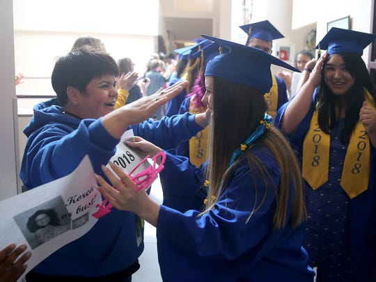 Bremerton High School graduating senior Kaley-Lynn Brocksome gets a hug from her mom, Kathleen, at the West Hills STEM Academy in Bremerton. Kaley-Lynn was inspired to get her degree after her mom got hers through an online program.