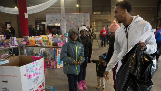 Pistons point guard Ish Smith, right, helps siblings Jameir Jamar, 9, Avonti Jamar, 11, and Khalil Jamar, 2, along with their mother, Jamil Jamar, select gifts during the annual Toys for Tots toy giveaway on Tuesday.