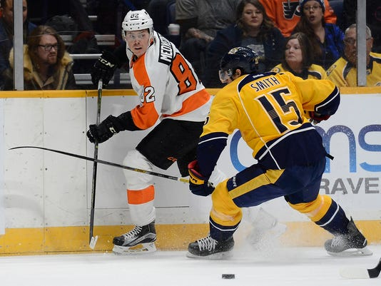 Philadelphia Flyers defenseman Evgeny Medvedev (82), of Russia, clears the puck away from Nashville Predators right wing Craig Smith (15) in the first period of an NHL hockey game Thursday, Feb. 4, 2016, in Nashville, Tenn. (AP Photo/Mark Zaleski)