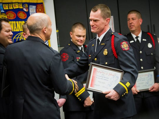 Evansville Fire Lt. Darryl Adler, right, is congratulated by other nominees after being named the Green River Kiwanis 2016 Firefighter of the Year at American Red Cross building in Evansville, Wednesday, March 22, 2017.