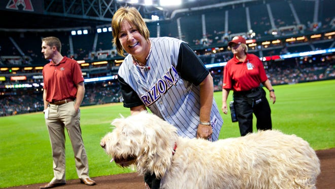 Susan Carpenter poses with Gus on Chase field before the D-Backs versus the Giants game.