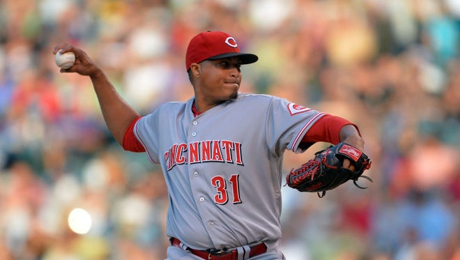 Cincinnati Reds starting pitcher Alfredo Simon (31) delivers a pitch in the second inning against the Colorado Rockies at Coors Field.