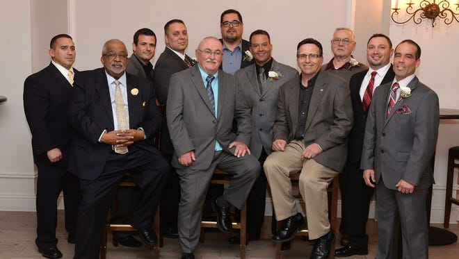 Members of the 1988 wrestling team, Shawn Tuck, coach Herman Petway, Frank Dagostino, Anthony Martinez, coach Dennis Miller, Adrian Lugo, Felix Martinez, coach Ron Franceschini, Jim Clay representing his late son Jeff Clay, Frank Dickinson, and Phillip Martinez (from left), at the Vineland High School All Sports Booster Club Hall of Fame banquet, Tuesday, Nov. 24 at Greenview Inn in Vineland.