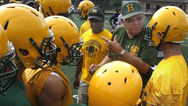 Farmington Hills Harrison football coach John Herrington gives directions to his players in 2011.