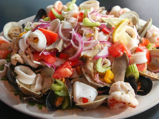 Seafood salad, (mussels, clams, calamari, scungilli and shrimp) prepared over mixed greens in a lemon garlic vinaigrette, is served at Vinnie's Clam Bar, located on Somerset Street in  Raritan, NJ, June 1, 2015.  Mary Iuvone/For The Courier News