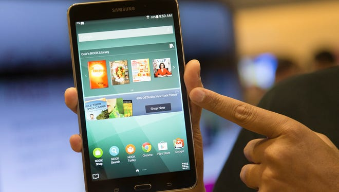A brand ambassador handles a new Samsung Galaxy Tab 4 Nook during the unveiling of the co-branded tablet that will replace B&N's Nook, Wednesday, Aug. 20, 2014, in New York. The 7-inch tablet will sell for $179 after a $20 instant rebate, the same entry price of the non-branded Samsung Galaxy Tab 4.
