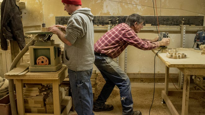Ken Foster, right, and his grandson Adam, work together in Ken's woodshop making butcher block trays in the shape of states in the U.S.