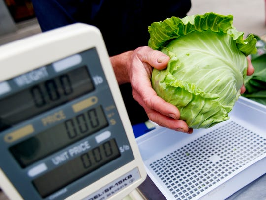 A head of lettuce is weighed during the opening day of the Market Square Farmers' Market in Knoxville on May 6, 2017.