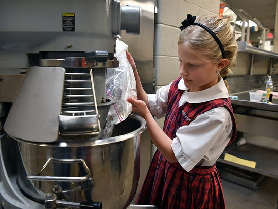 Christ Academy third grader Nikki Goodgion adds ingredients