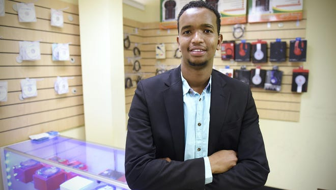 Mohamed Jama Mohamud stands Thursday, Aug. 13, in his small store in St. Cloud. Mohamud programs devices to receive television channels from throughout the world and installs those devices in customer's homes.